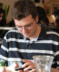 Photo of Matt Bowsher in indian restaurant tweeting on his phone