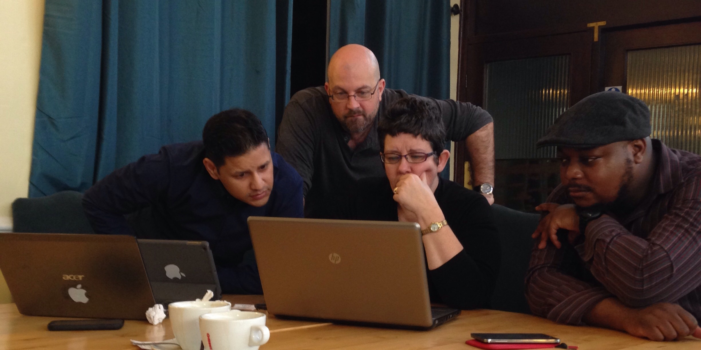 Photo of Deepak, Lorraine and Carl, huddled around a laptop in deep concentration, with Jon behind them leaning in