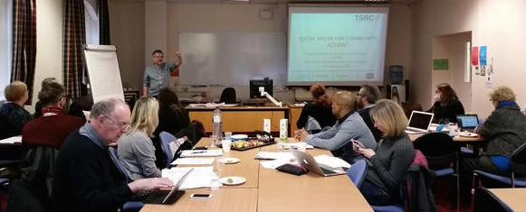 Photo from research seminar, Angus McCabe at the front of a seminar room, participants looking towards him or using laptops etc.