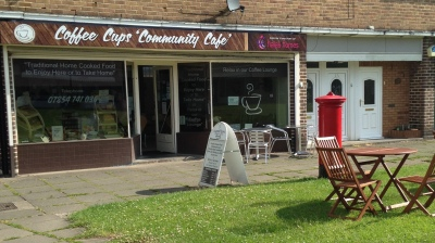 Photo of Coffee Cups Community Cafe from outside, with chairs on the grass in front of the cafe