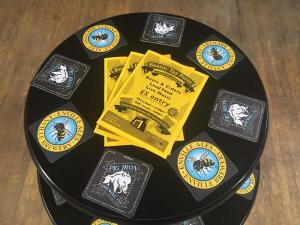 photo of Bostin Tay Party flyers and beer mats on a black table