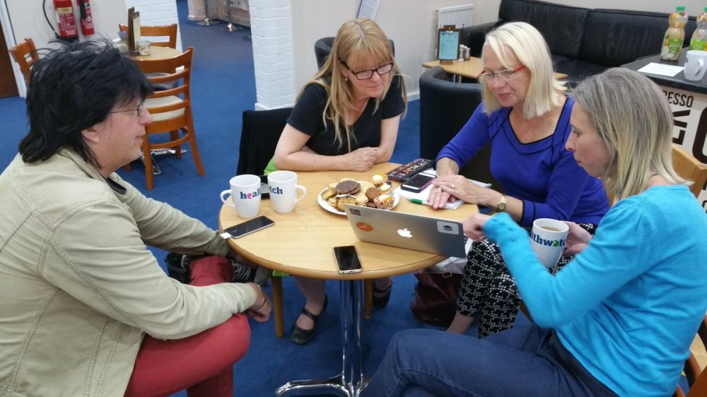 Photo of Neale, Tracey, Sue and Lorna around a laptop in DY1 coffee shop